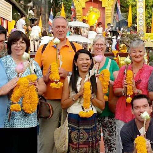 Private tour guide Wilai standing with clients at temple in Chiang Mai.